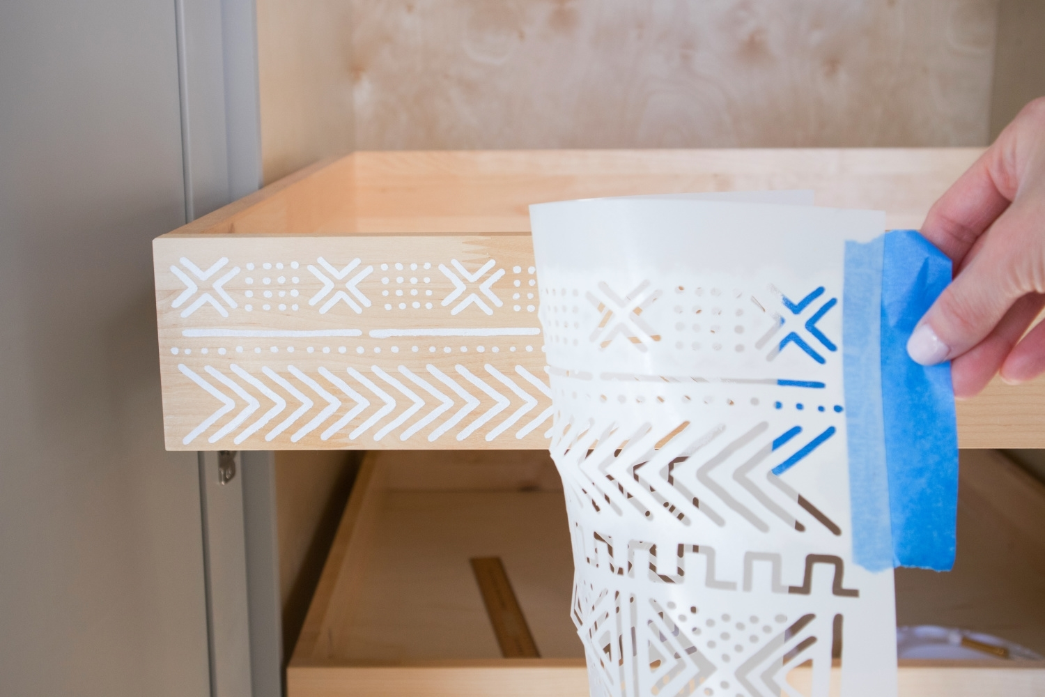 Use a stencil and acrylic paint to decorate drawers